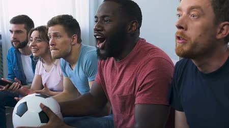 roaring : Group of friends watching football on tv, roaring approval after scored goal