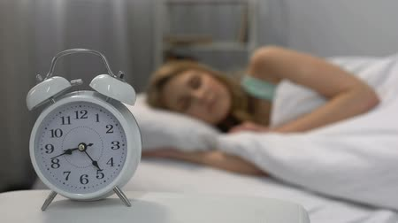 deprivation : Female sleeping in morning, alarm clock near bed, day routine, time management Stock Footage