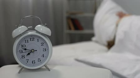 deprivation : Sleeping woman closing ears pillow irritated by ringing alarm clock, jet lag Stock Footage