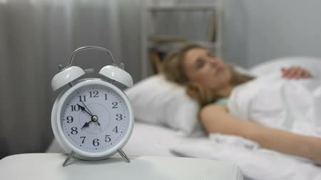 deprivation : Lady throwing pillow at ringing alarm clock, sleep deprivation, morning stress