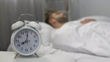 deprivation : Angry man throwing pillow at ringing alarm clock, morning routine, laziness Stock Footage
