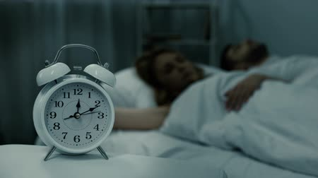 fáze : Married couple peacefully sleeping at night with clock near bed, sleep phases