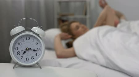 fáze : Happy couple waking up with alarm clock in morning and kissing in bed, family