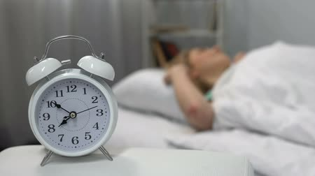 deprivation : Female waking up easily to ringing alarm clock in morning, healthy lifestyle