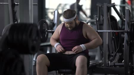 umma : Upset man looking at his fat stomach, desire to lose weight, gym workout, sport Stok Video