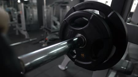 ingrassare : Trainer putting and removing weight plates from barbell, preparing gym equipment Filmati Stock