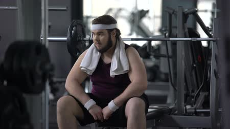 pozitivní : chubby man in gym feeling upset because of excess weight, shyness