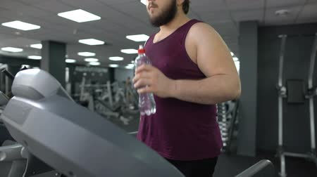 leden : Sweaty sportsman exercising on treadmill and drinking water, cardio workout
