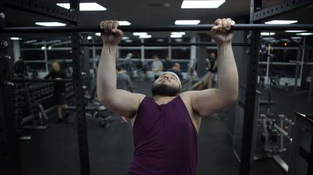 çekme : Overweight man trying to pull up on sport bar, weak body muscles, gym training