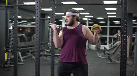 refusing : Obese man holding dumbbell eating burger, refusing from doing sport, addiction Stock Footage