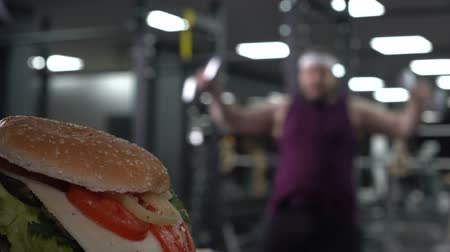 willpower : Chubby man jumping with dumbbells looking at tasty burger, personal motivation