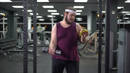 sports nutrition : Obese man lifting dumbbell and holding burger in hand, life decision, motivation Stock Footage