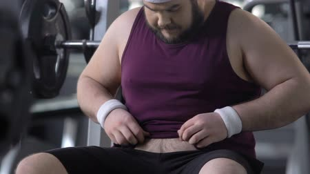 воля : Unconfident overweight male in gym looking at his fat belly, weight loss dieting Стоковые видеозаписи