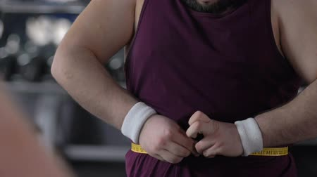 bel ölçüsü : Happy fat man measuring belly with tape in gym, weight loss achievement .