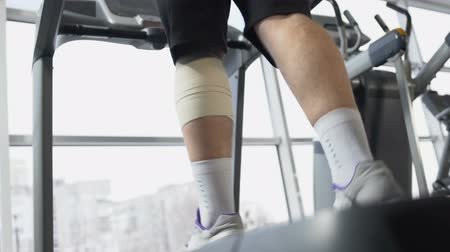 штамм : Male with injured leg muscle walking on treadmill in gym, recovery, will power Стоковые видеозаписи