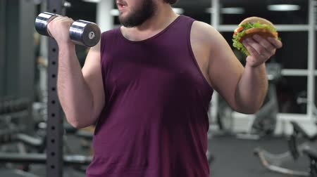 seçme : Obese male with dumbbell in hand eating hamburger. Stok Video