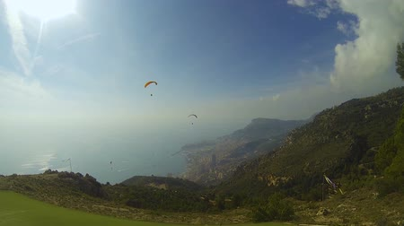 riskli : Couple of paragliders drifting over hills down towards seaside city, extreme