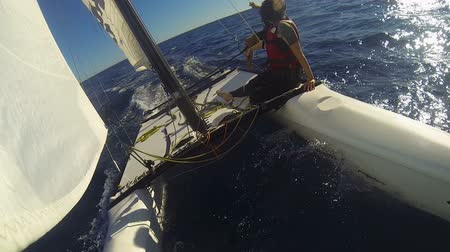 riskli : Windsurf catamaran going rapidly in ocean with two people on edge, extreme
