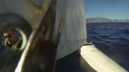 kaptan : Windsurfing catamaran moving quickly across sea, man face captured through hole Stok Video