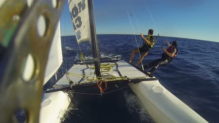 riskli : Fastened by ropes catamaran windsurfers overhanging hull, waving at passing bird