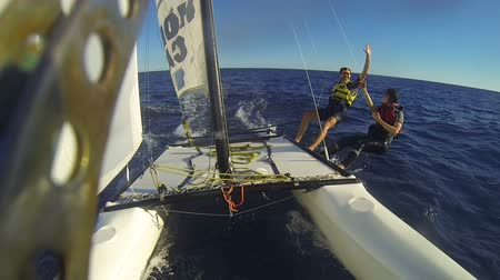 encouraging : Catamaran under sail at high speed, people aside the hull high-fiving each other Stock Footage