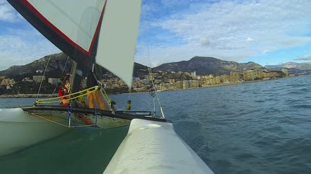 cascos : Windsurfing catamaran moving away from coastal city with a few people on board