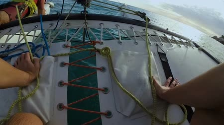 cascos : Person sailing on windsurfing catamaran on tied up together by ropes trampoline