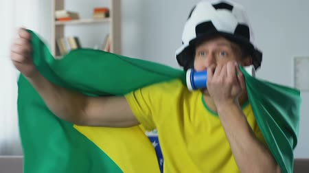 brazil : Brazil supporter watching football game on TV, blowing fan horn and cheering