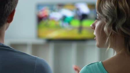 motivo : Displeased woman quarreling with husband watching football on TV.