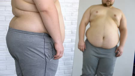 уродливый : Obese man suffering from belly excess weight, looking in mirror, health problem Стоковые видеозаписи