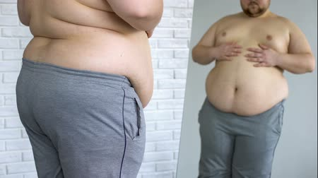 смазка : Sad overweight man looking at fat belly mirror reflection, weight loss problem