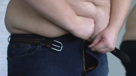apertado : Overweight man zipping up jeans, suffering from stomach fat, hormonal disease