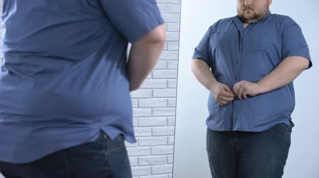 пухлый : Plump man buttoning up tight shirt, oversize clothing problem, appearance Стоковые видеозаписи