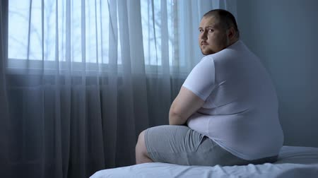 hasi : Sad heavy man sitting on bed at home, health problem, depression, insecurities