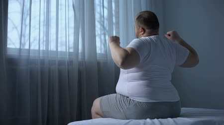 упитанность : Overweight heavy male doing morning exercises sitting on bed, stretching muscles