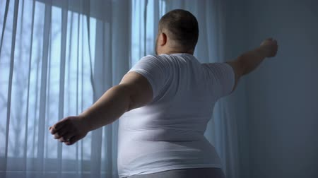 упитанность : Fat man stretching back muscles, feeling heavy and uncomfortable, poor mobility
