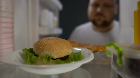 упитанность : Fat hungry man taking hamburger from fridge and eating eagerly, diet failure Стоковые видеозаписи