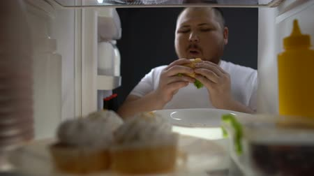 упитанность : Fat man chewing hamburger in front of fridge, junk food addiction, obesity