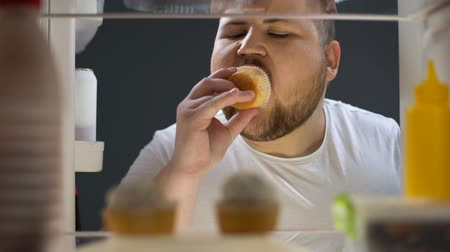 iştah : Overweight man opening fridge and eating delicious cream cake at night, dieting