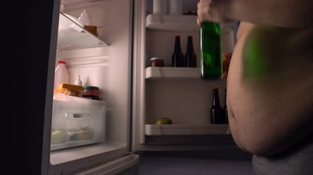 ivászat : Lazy obese bachelor eating junk food from fridge and drinking beer, calories