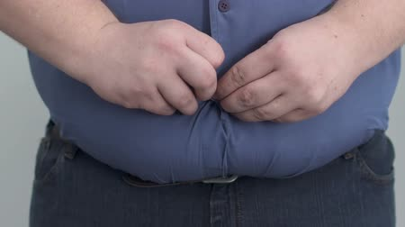 umbigo : Obese man buttoning shirt on enormous tummy, fight with insecurities.