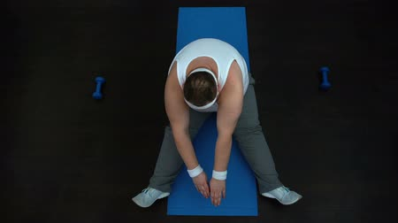 fárasztó : Tired overweight man stretching on mat after home workout, slimming program
