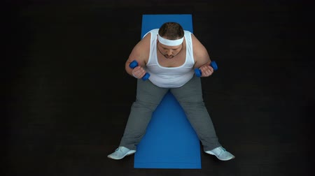 pumping : Chubby male sitting on mat doing biceps curls with dumbbells pumping arm muscles Stock Footage