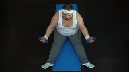 biceps curls : Tired obese male doing dumbbells exercise at home, ineffective training program Stock Footage