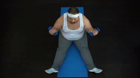 biceps curls : Active fat man lifting dumbbells sitting on mat, sport motivation, discipline Stock Footage