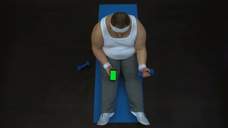 воля : Lazy fat man lifting dumbbell and watching video on smartphone, burning calories