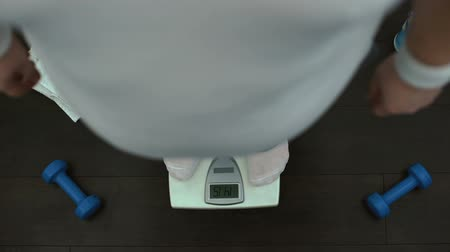 tartmak : Obese man standing on gym scale, checking weight, slimming training, dieting