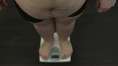 tartmak : Big belly man standing on measuring scales for checking weight, diet result Stok Video
