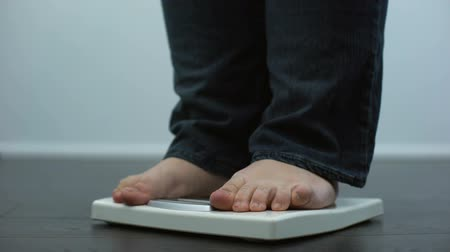 tartmak : Plump male checking body weight on scales, health disorder, overeating result Stok Video