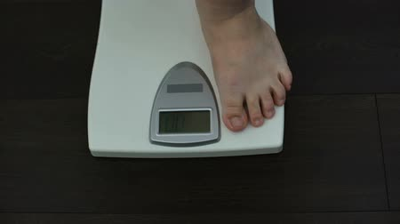 tartmak : Man checking weight loss on scales, unhealthy nutrition, genetic predisposition